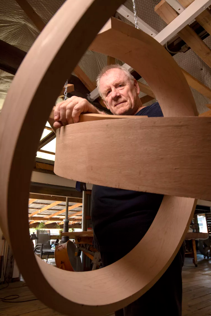 rick maxwell standing by his bent wood sculpture